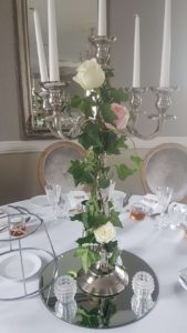 silver-candelabra-wrapped-with-ivory-roses-min